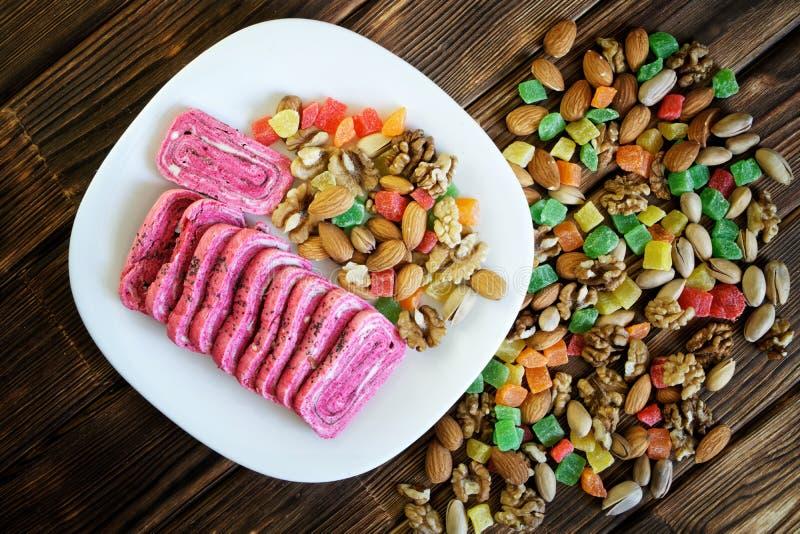 阿拉伯东方甜点:在一块白色板材的非凡桃红色halvah在开心果、杏仁、核桃和脯旁边 库存图片