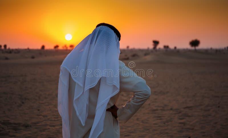 阿拉伯人在沙漠单独站立 库存照片