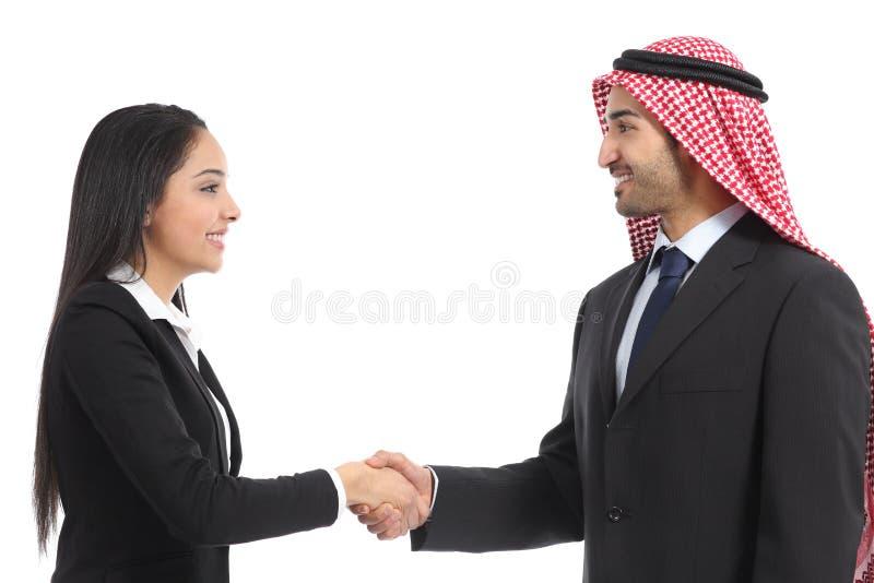 阿拉伯人沙特买卖人握手的侧视图 免版税图库摄影