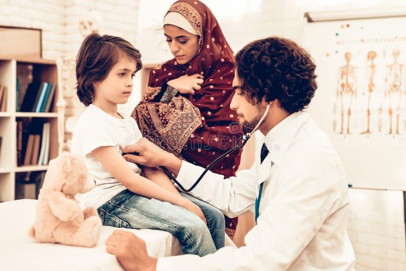 阿拉伯医生Checking Heartbeat一个小男孩 阿拉伯女性医生Examining一个小男孩 儿科医生的孩子 医院 免版税库存照片