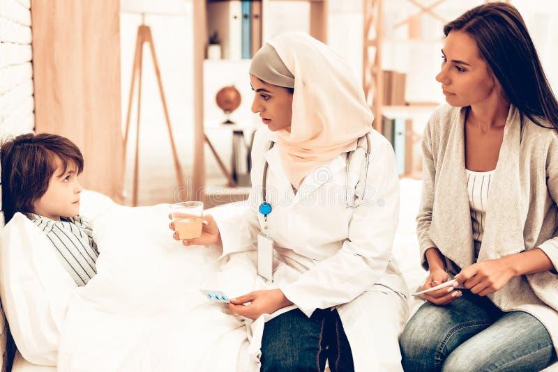 阿拉伯医生Give Medicine病的男孩说谎的床 库存图片
