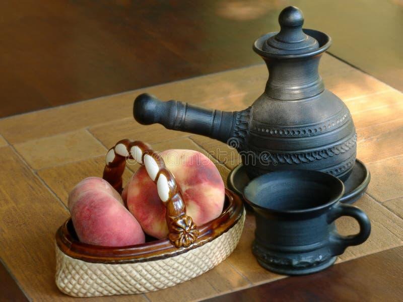 阿拉伯咖啡罐和陶瓷花瓶用桃子 库存图片