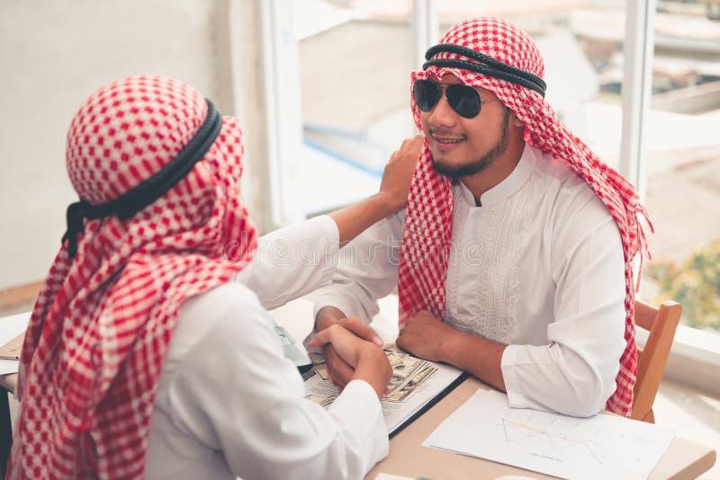 阿拉伯商人是握手在成功成交以后 握手的阿拉伯商人画象对他的商务伙伴  免版税库存照片