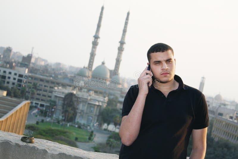 阿拉伯埃及年轻商人谈话与电话 免版税库存照片