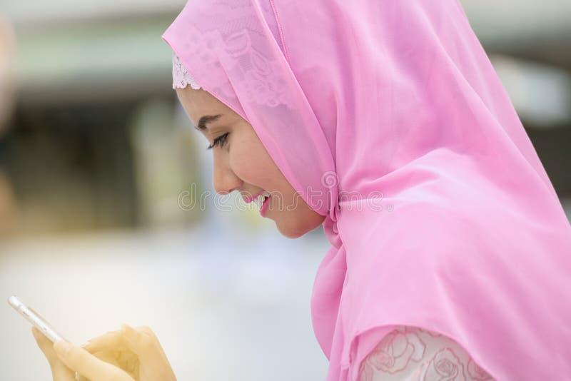 阿拉伯女商人微笑愉快使用手机和moder 免版税库存图片