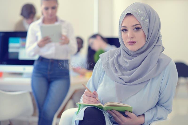 阿拉伯女实业家在有工作在背景中的队的起始的办公室, 库存照片