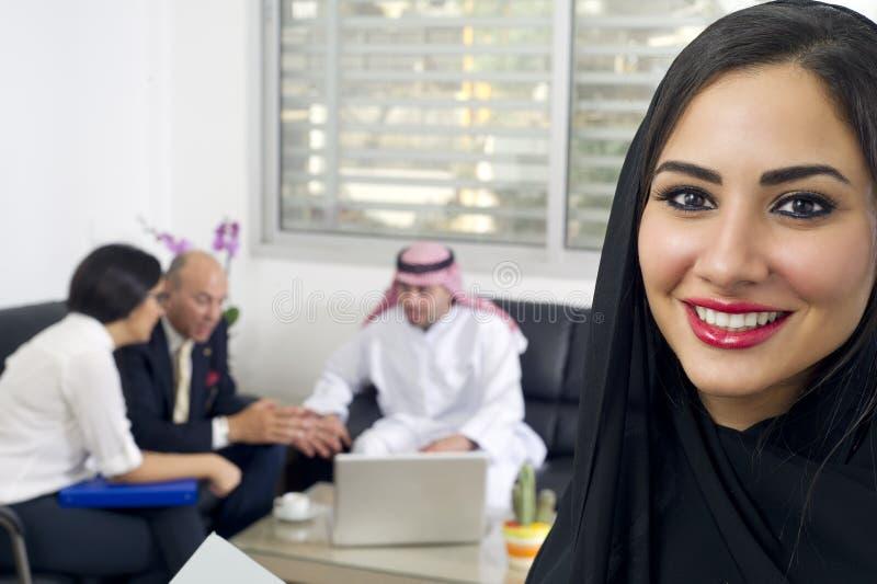 阿拉伯女实业家在有见面在背景中的买卖人的办公室 图库摄影
