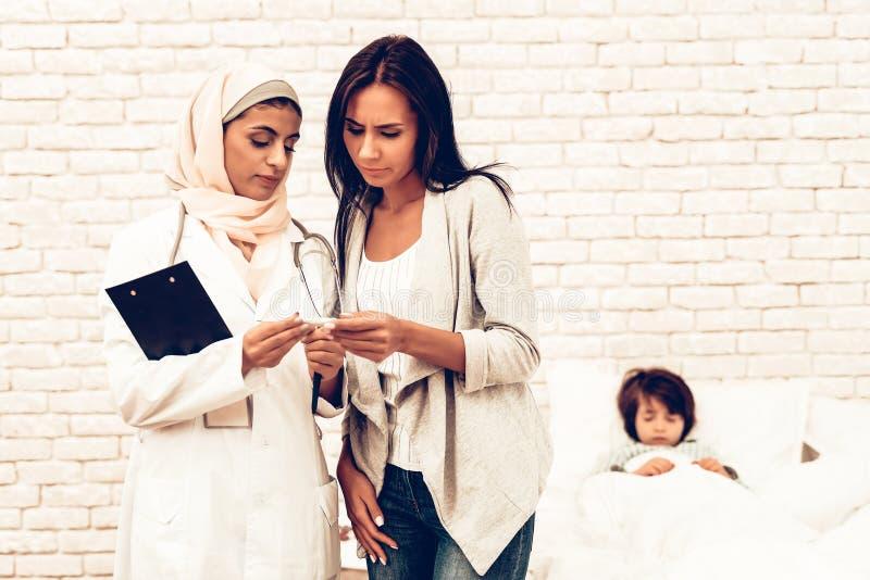 阿拉伯女性儿科医生任命病的男孩 免版税库存照片
