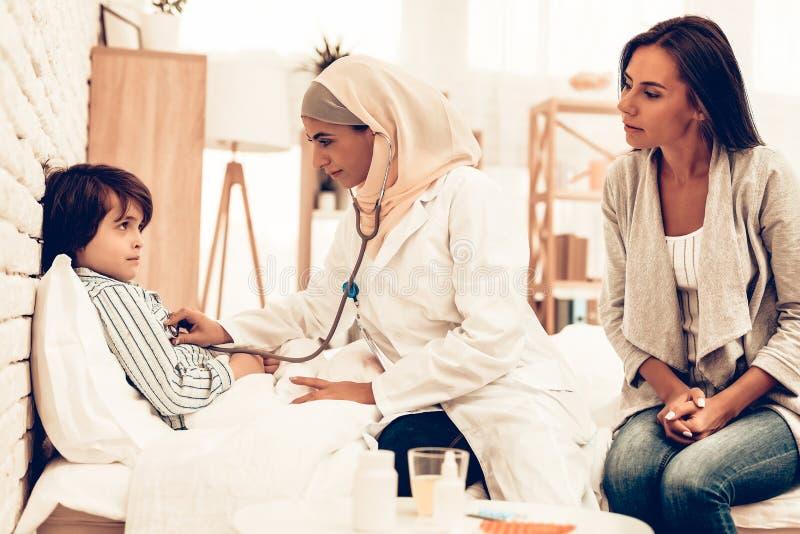 阿拉伯女性医生Examining一个小男孩 库存照片