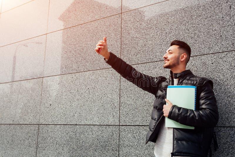 阿拉伯学生采取在智能手机的selfie外面 愉快的人看电话由墙壁在等待朋友的类以后 库存照片