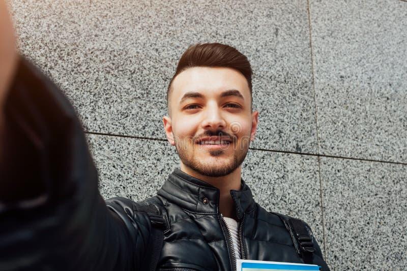 阿拉伯学生采取在智能手机的selfie外面 愉快的人看电话由墙壁在类以后 库存照片
