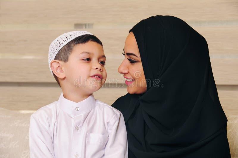 阿拉伯家庭、母亲和儿子坐长沙发 免版税图库摄影