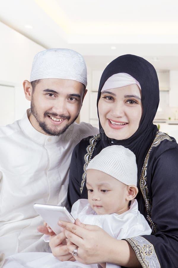 阿拉伯家庭在家拿着智能手机 免版税库存照片