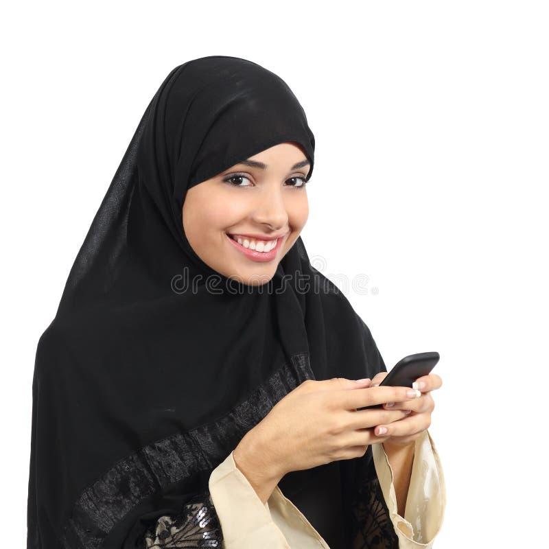 阿拉伯沙特使用一个巧妙的电话的酋长管辖区微笑的妇女 免版税图库摄影