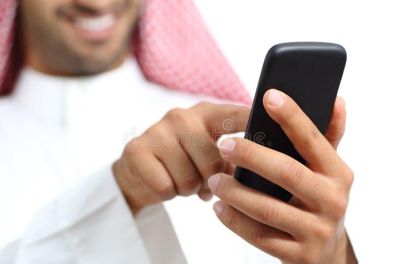阿拉伯沙特酋长管辖区供以人员发短信在一个巧妙的电话的手 库存照片