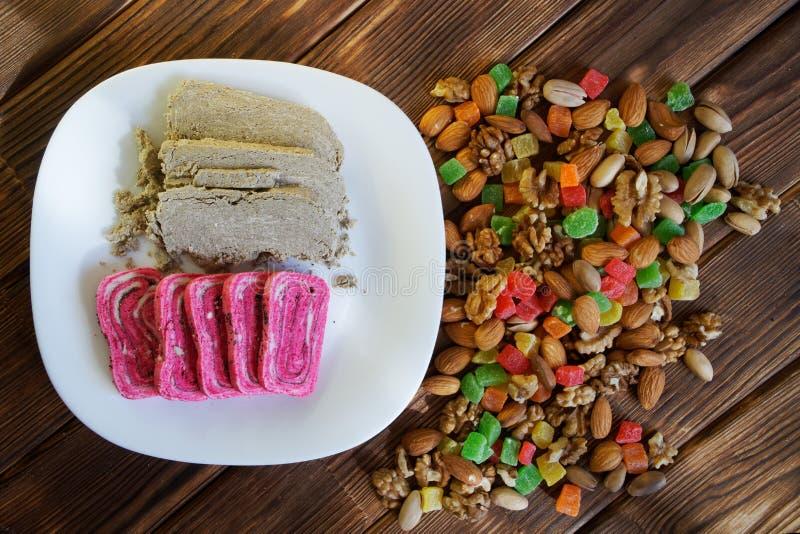 阿拉伯甜点:异常的桃红色和传统灰色halvah在一块白色板材在脯、开心果、杏仁和核桃旁边 免版税库存照片