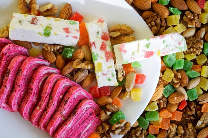 阿拉伯甜点:异常的桃红色halva和白色喉片在脯、开心果、杏仁和核桃旁边 全国东方人 免版税图库摄影