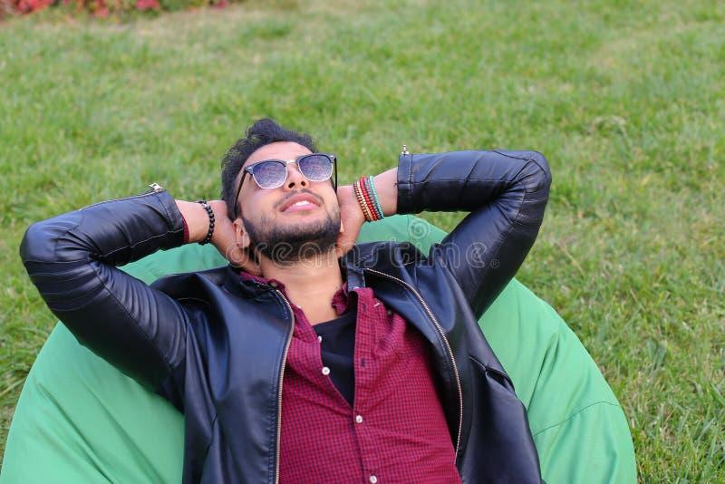 年轻阿拉伯男性人,学生画象在椅子, Smilin说谎 库存照片