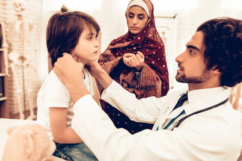 阿拉伯男性医生Examining一个小男孩 儿科医生的孩子 医院概念 健康的概念 儿童患者参观 库存图片