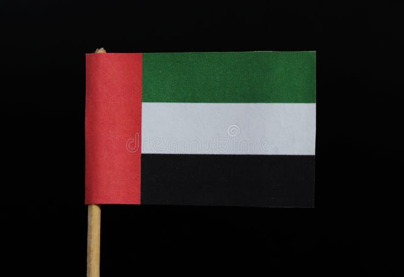 阿拉伯联合酋长国的一面正式旗子牙签的在黑背景 一水平三色绿色,白色和黑 免版税库存照片