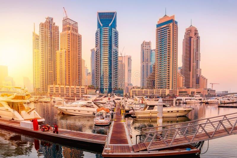 阿拉伯联合酋长国的迪拜码头湾区,日落时分有船只和摩天大楼 图库摄影