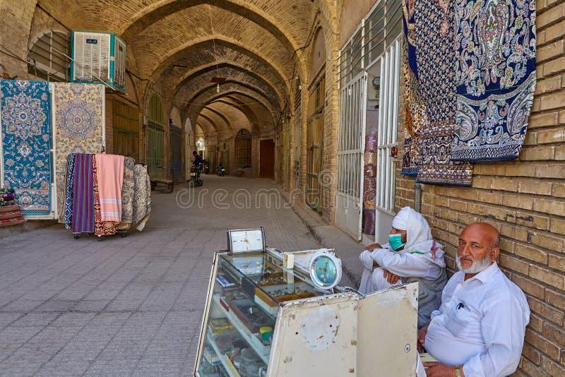 阿拉伯贸易商在被成拱形的车道附近坐在义卖市场,亚兹德,伊朗 库存图片
