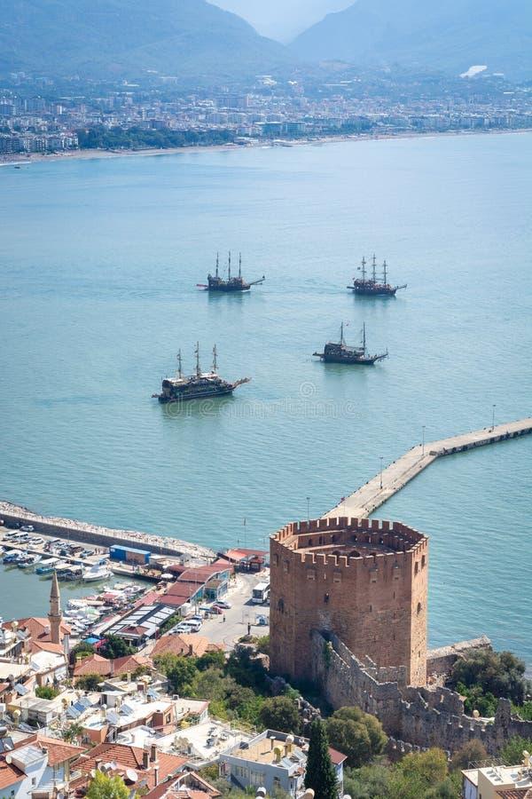 阿拉尼亚港口、船和Kizil Kule红色塔,阿拉尼亚城堡古老石墙看法  Alanya,土耳其 库存照片