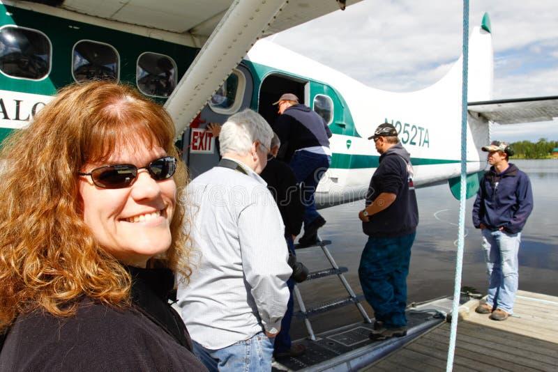 阿拉斯加-妇女搭乘浮动飞机 免版税库存图片