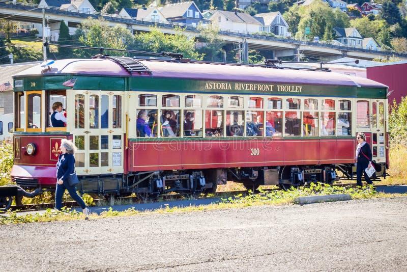 阿斯托利亚采取在游览中的河边区台车游人在使用老货物铁轨的街市阿斯托利亚附近 免版税库存照片