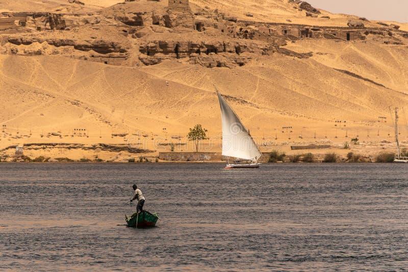 阿斯旺,埃及21 05 2018年他的钓鱼在河的中心的小船的渔夫 免版税库存图片