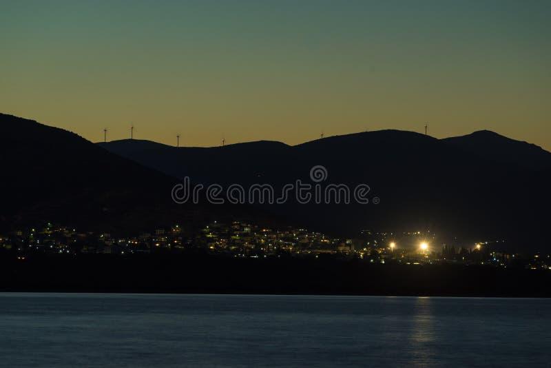 阿斯特罗斯镇在晚上希腊,在小山的风轮机 库存照片