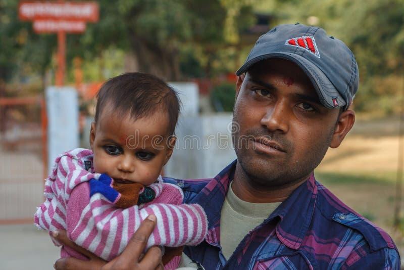 阿格拉,印度- 2012年12月:印地安家庭,拿着他的膝部的父亲女儿 免版税库存照片
