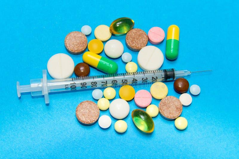 阿片样物质流行病 阿片样物质药片 吸毒概念-另外色的药片和注射器在蓝色背景 库存图片
