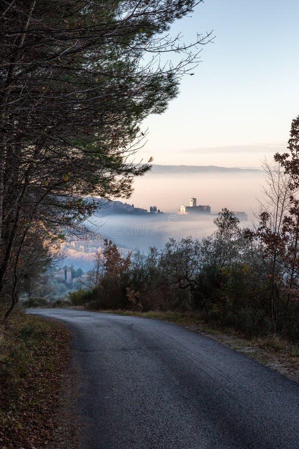 阿西西镇翁布里亚的圣弗朗西斯教堂,在雾海中,在一条路的尽头,有一幅超现实且不寻常的景象 库存照片