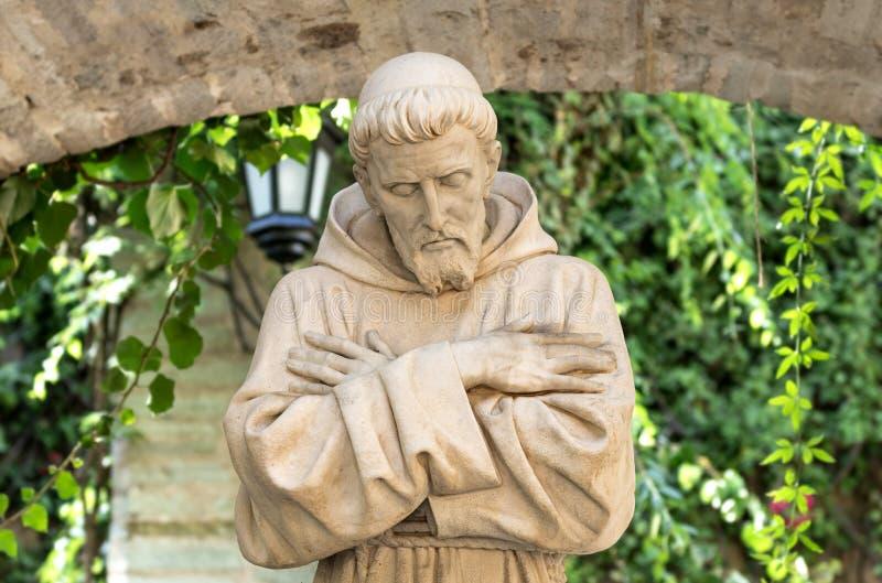 阿西西雕象圣法兰西斯在殖民地庭院里 免版税库存图片