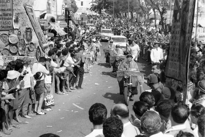 阿马飞,意大利,1960年-火炬持票人行军通过阿马飞街道在两个人群翼之间的有他的火炬的向罗马为 库存图片