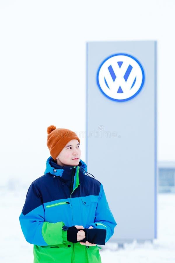 阿巴坎,俄罗斯- 2016年1月3日 站立在VW经销权标志前面的人 免版税库存图片