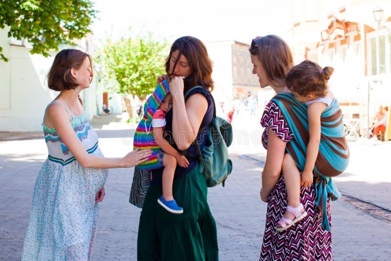 附件parrenting的概念 遇见她的朋友的怀孕的夫人 免版税库存图片