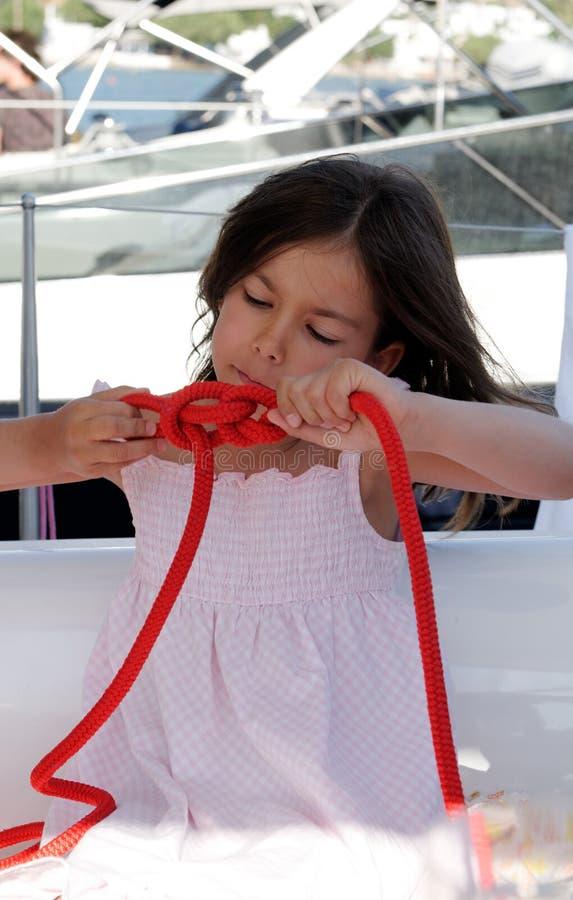 附加在绳索的女孩结 免版税库存照片