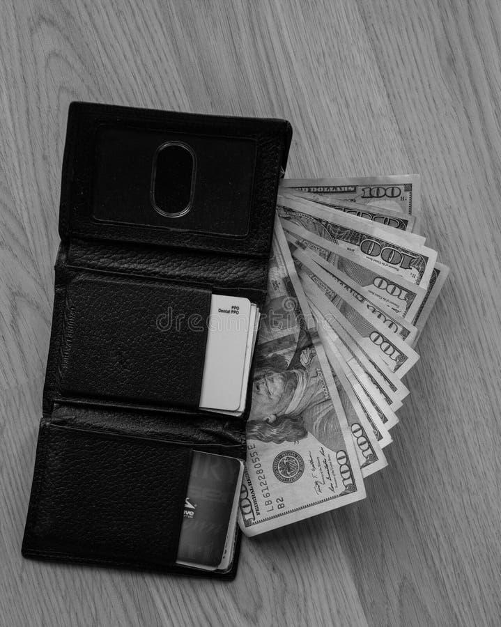 黏附在人的黑钱包外面的金钱 B&W 库存图片