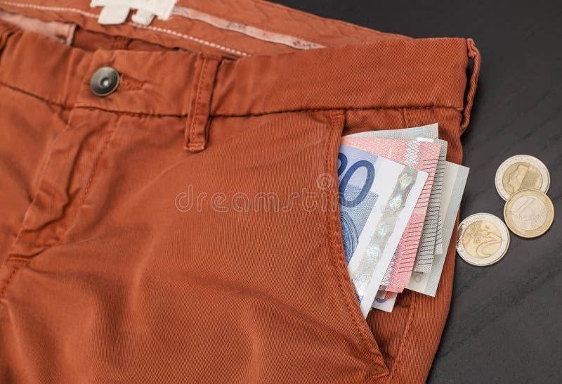 黏附在他的裤子口袋和硬币外面的欧洲纸币在桌 库存图片