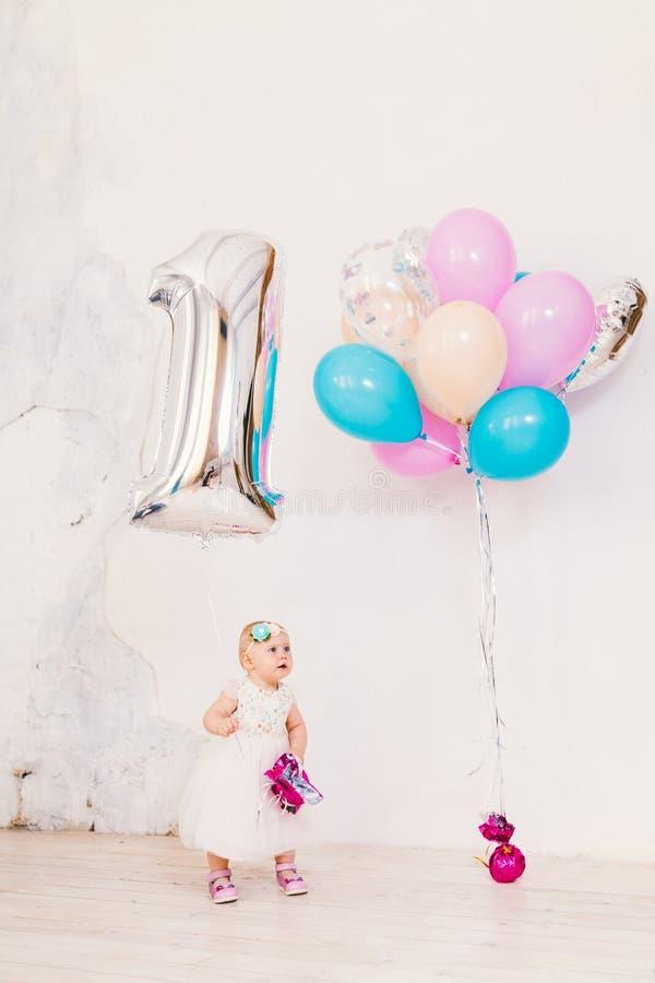 附属的儿童的生日是childs一年 小女孩在明亮的屋子里对白色墙壁在礼服和白肤金发的藏品 图库摄影
