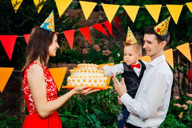 附属的儿童` s生日聚会、食物和甜点 一个年轻家庭庆祝一年儿子 爸爸拿着一个大蛋糕,妈妈是 免版税库存照片