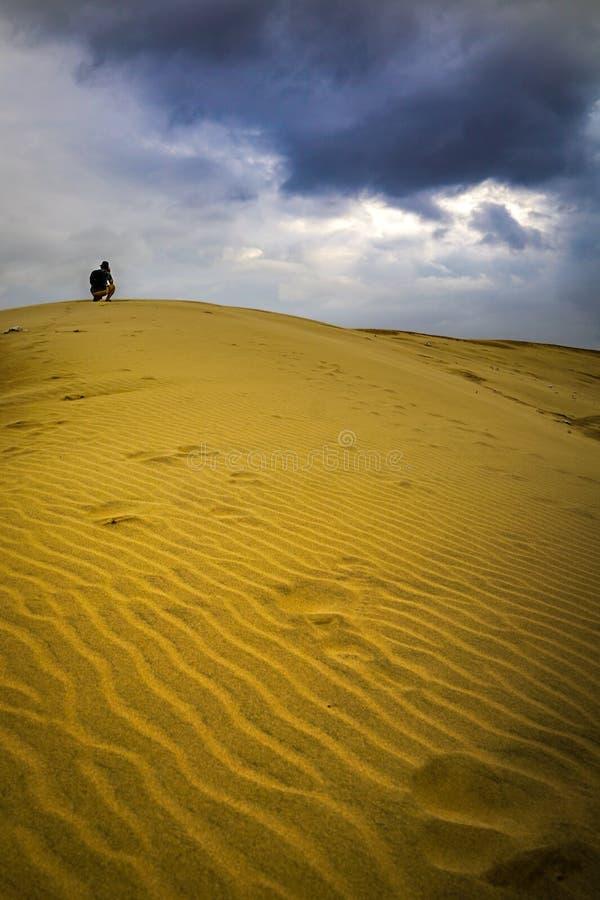 附带探险家的摄影师在沙漠山顶部 免版税库存照片