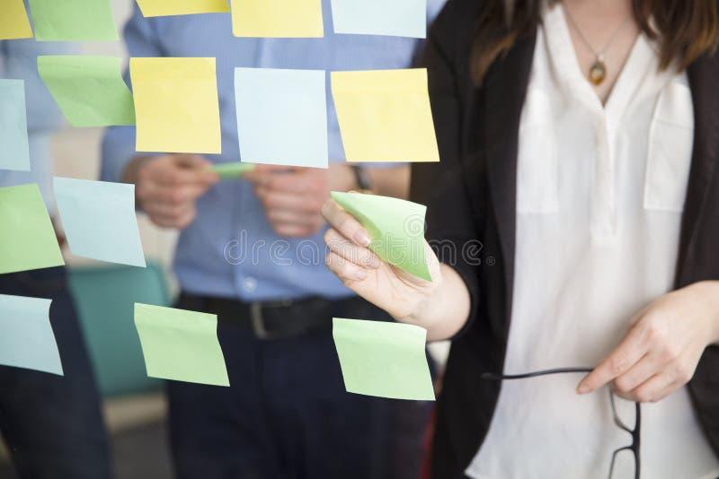 黏附笔记的女实业家的中央部位,当支持执行委员时 免版税库存照片