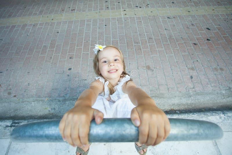 附近使用与路的白色礼服的微笑的儿童女孩在城市 库存照片