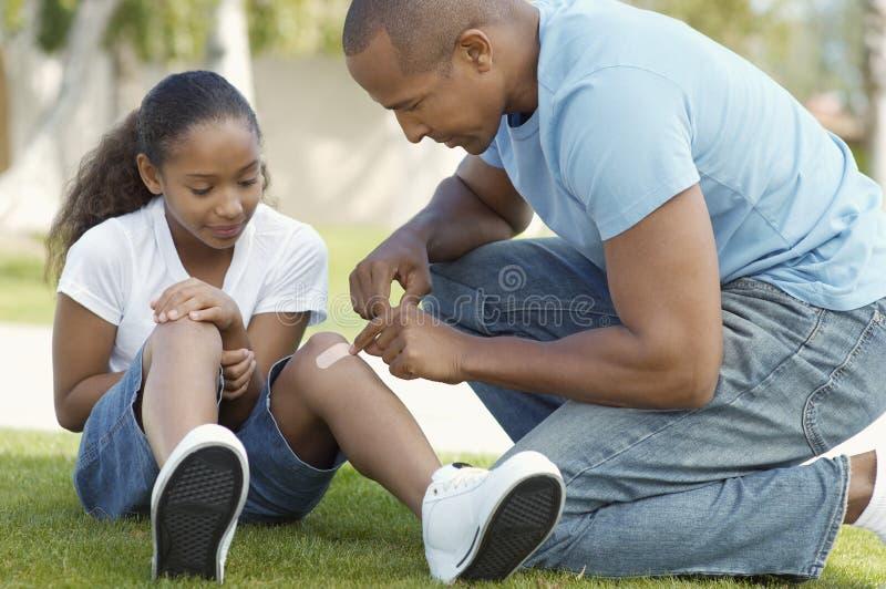黏附绷带的父亲对女儿的膝盖在公园 库存照片