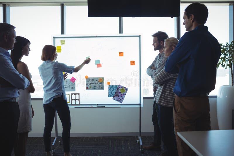黏附黏着性笔记的女实业家在whiteboard,当站立在办公室时的同事 免版税库存照片