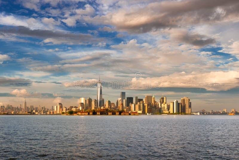 降低曼哈顿财政区摩天大楼和埃利斯岛黄昏的从纽约港口 库存图片