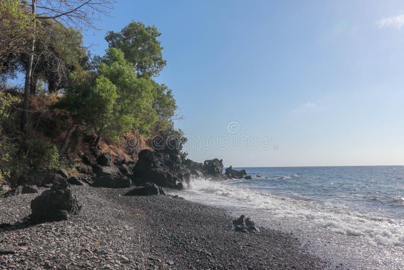 陡峭的高熔岩岩石峭壁在巴厘岛东部  黏附在水外面的孤零零岩石 黑沙滩 蓝色海天线 免版税库存图片
